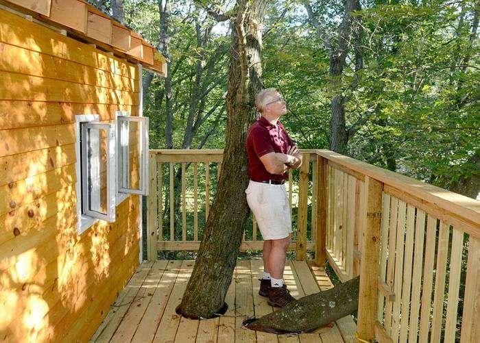 Jay Hewitt на фоне своего дома на дереве.