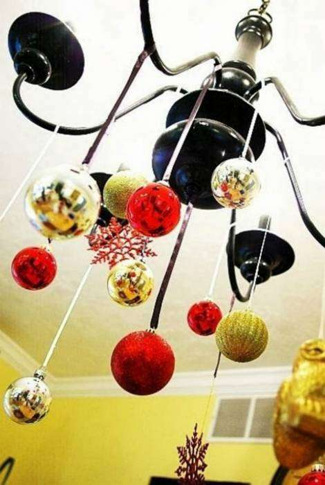 Люстра, украшенная дождиками и елочными шарами прекрасно дополнит атмосферу праздника.