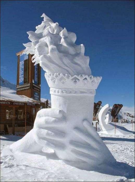 Снежная скульптура, изображающая руки, которые держат Олимпийский огонь.