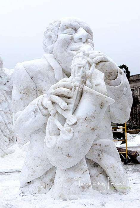 Снежная скульптура в виде уличного музыканта.