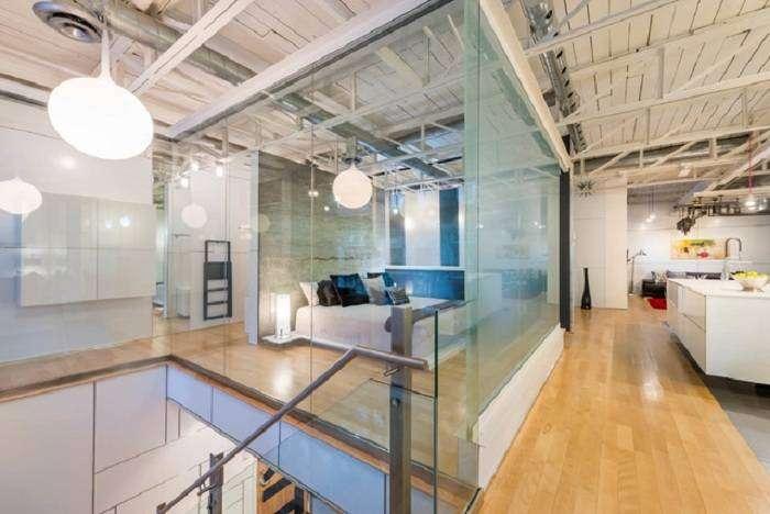 Пространство спальной увеличивается за счет стеклянных стен, которые расширяют представление о промышленном дизайне.