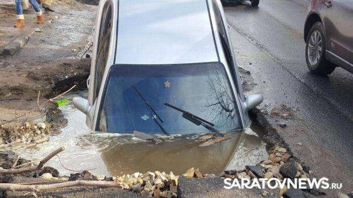 В Саратове автомобиль провалился в огромную яму на дороге (6 фото)