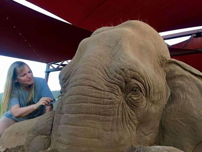Песочная скульптура, изображающая слона и мышь, играющих в шахматы
