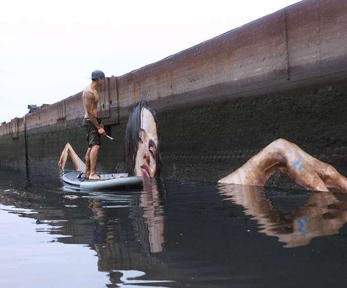 Художник рисует потрясающие картины у воды, стоя на доске для серфинга
