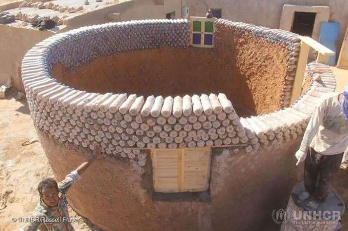 Парень строит дома, используя вместо кирпичей бутылки с песком