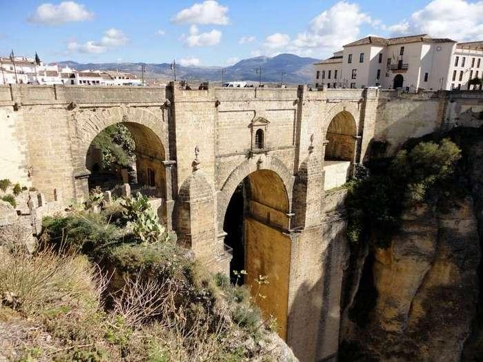 Ронда - город, парящий в облаках <br><br>Он расположен в 40 километрах от побережья Средиземного моря на горном ущелье, по обеим сторонам этого раскола. Население города составляет примерно 37000 жителей.<br /> <img class=