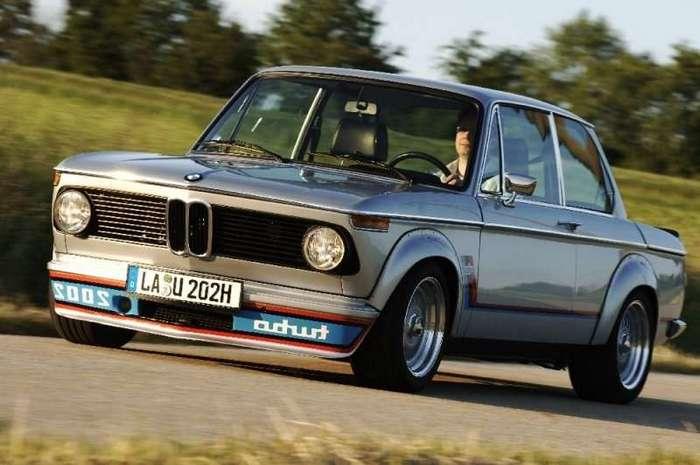 Нескучная история: BMW 2002 Turbo <br><br><i>Несмотря на то, что ни одна машина не была сделана для Англии (в первую очередь из-за расположения турбины с правой стороны), некоторые автомобили после покупки переделывались дилерами в Великобритании на правый руль и расходились по странам с левосторонним движением (Австралия, Япония)</i><br><br><br><br>Шумиха, поднятая вокруг машины и проблемы с турбиной сдвинули первоначальные планы по производству с апреля 1973 года на январь 1974. Но, несмотря на все преграды, Turbo начала выпускаться. От начала и до конца проект защищал Боб Лутц (который позже подарит нам Dodge Viper и новый Chevrolet Camaro) — в тот самый момент он работал в BMW перед своим уходом в Ford.<br /> <br><br><br><br>Процесс управления автомобилем делился на две совершенно разные части: до 4000 оборотов и после. В нижнем диапазоне оборотов это был ленивый мотор, в котором можно было и не признать двухлитровую родословную, но как только стрелка тахометра становилась вертикально (4000 об/мин), «дветысячивторая» кидалась вперёд с энергией Ленина на трибуне, взывающего к коммунизму. Длинный впускной тракт и инерционность большой грузовой турбины делали включение наддува настолько резким, что узенькие «велосипедные» шины шириной всего 185 мм не выдерживали лавины 240 ньютон-метров и неизменно срывались в пробуксовку. Из-за этого в поворотах BMW 2002 Turbo постоянно перебегали дорогу деревья и канавы, а машине не дали ярлык «widow-maker» («делающая вдовой») лишь из-за небольшого объёма производства. Правда, из 1660 серийных экземпляров в живых на сегодняшний день осталось всего около 500.<br /> <img class=
