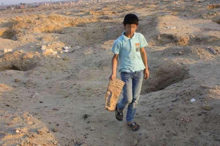 Египет. Калейдоскоп фотографий <br><br><b> <b>Ребенок с древним артефактом среди ям, вырытыми черными копателями на территории некрополя Абусир</b> </b><br><img class=