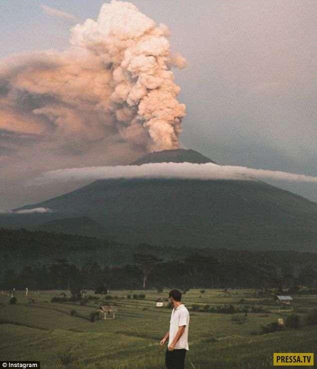 """Туристы радостно фотографируются на фоне """"ожившего"""" вулкана на Бали (14 фото)"""